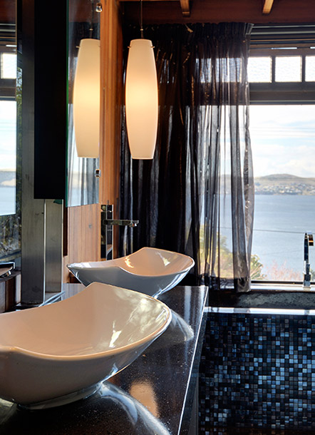 Timber based bathroom with 2 white vanity basins looking toward water views